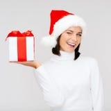 Donna sorridente in cappello dell'assistente di Santa con il contenitore di regalo Fotografie Stock Libere da Diritti