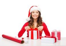 Donna sorridente in cappello dell'assistente di Santa con il contenitore di regalo Immagine Stock Libera da Diritti