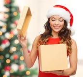Donna sorridente in cappello dell'assistente di Santa con il contenitore di regalo Fotografie Stock
