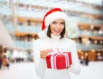 Donna sorridente in cappello dell'assistente di Santa con il contenitore di regalo Immagini Stock Libere da Diritti