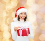 Donna sorridente in cappello dell'assistente di Santa con il contenitore di regalo Fotografia Stock