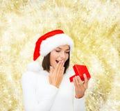 Donna sorridente in cappello dell'assistente di Santa con il contenitore di regalo Immagine Stock