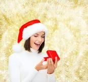Donna sorridente in cappello dell'assistente di Santa con il contenitore di regalo Immagini Stock