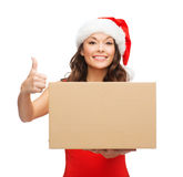 Donna sorridente in cappello dell'assistente di Santa con la scatola del pacchetto Fotografie Stock