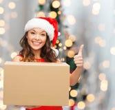 Donna sorridente in cappello dell'assistente di Santa con la scatola del pacchetto Immagini Stock
