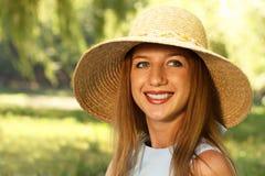 Donna sorridente in cappello di paglia Immagini Stock Libere da Diritti