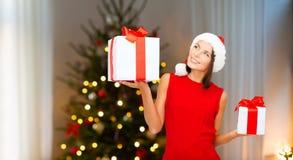 Donna sorridente in cappello di Santa con i regali di natale immagine stock