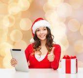 Donna sorridente in cappello di Santa con il pc della compressa e del regalo Immagini Stock