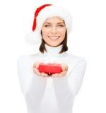 Donna sorridente in cappello di Santa con il piccolo contenitore di regalo Fotografia Stock Libera da Diritti