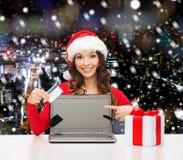 Donna sorridente in cappello di Santa con il regalo ed il computer portatile Immagini Stock Libere da Diritti