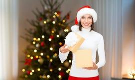 Donna sorridente in cappello di Santa con il regalo di natale fotografie stock