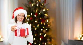 Donna sorridente in cappello di Santa con il regalo di natale immagine stock