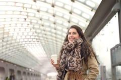 Donna sorridente in cappotto con caffè alla stazione fotografia stock
