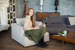 Donna sorridente casuale che per mezzo del computer portatile grigio Immagine Stock Libera da Diritti
