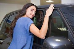 Donna sorridente che abbraccia un'automobile nera Immagini Stock