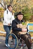 Donna sorridente che aiuta suo padre disabile Immagine Stock Libera da Diritti