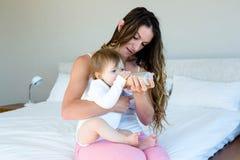 donna sorridente che allatta con il biberon un bambino Immagine Stock Libera da Diritti
