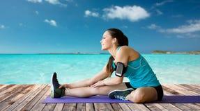 Donna sorridente che allunga gamba sulla stuoia sopra il mare Fotografia Stock