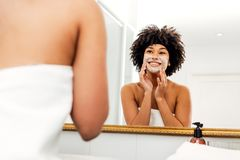 Donna sorridente che applica crema naturale fotografie stock libere da diritti