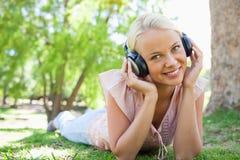 Donna sorridente che ascolta la musica mentre trovandosi Immagini Stock Libere da Diritti