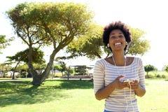 Donna sorridente che ascolta la musica in parco con lo Smart Phone immagine stock libera da diritti