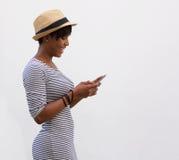 Donna sorridente che cammina e che legge messaggio di testo Immagine Stock