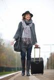 Donna sorridente che cammina sulla piattaforma della stazione ferroviaria Immagine Stock