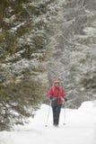 Donna sorridente che cammina sulle precipitazioni nevose nevose della pista un U. Immagini Stock