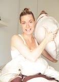 Donna sorridente che cattura scopo con un cuscino Immagine Stock