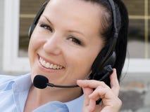 Donna sorridente che comunica dalla cuffia Immagini Stock Libere da Diritti