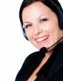 Donna sorridente che comunica dalla cuffia fotografia stock