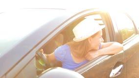 Donna sorridente che conduce un'automobile al tramonto stock footage
