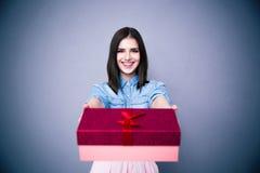 Donna sorridente che dà un contenitore di regalo alla macchina fotografica Immagine Stock