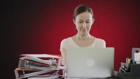 Donna sorridente che digita sul computer portatile video d archivio