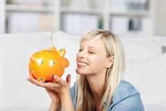 Donna sorridente che esamina il suo porcellino salvadanaio Fotografia Stock