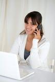 Donna sorridente che esamina voi e per mezzo del suo computer portatile Fotografia Stock Libera da Diritti