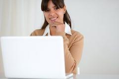 Donna sorridente che esamina voi e per mezzo del suo computer portatile Fotografie Stock Libere da Diritti