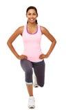 Donna sorridente che esegue allungando gli esercizi di affondo Immagini Stock Libere da Diritti