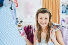 Donna sorridente che fa acquisto che esamina la macchina fotografica Fotografia Stock