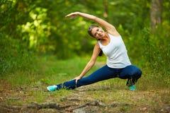 Donna sorridente che fa allungando esercitazione Fotografia Stock
