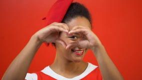 Donna sorridente che fa cuore con le mani, gentilezza, lavoro di carità, fondo rosso stock footage