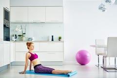 Donna sorridente che fa esercizio di forma fisica a casa Fotografie Stock