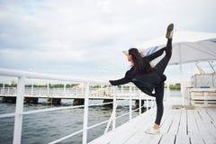 Donna sorridente che fa esercizio di yoga all'aperto sul pilastro della spiaggia Immagini Stock Libere da Diritti