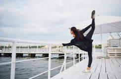Donna sorridente che fa esercizio di yoga all'aperto sul pilastro della spiaggia Fotografie Stock Libere da Diritti
