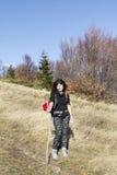 Donna sorridente che fa un'escursione in un'alta montagna Fotografia Stock