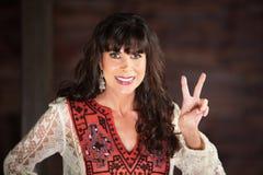 Donna sorridente che fa un gesto di V immagini stock libere da diritti