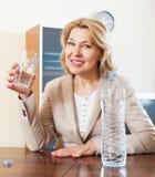 Donna sorridente che giudica vetro riempito di acqua Immagini Stock Libere da Diritti