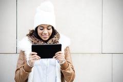Donna sorridente che guarda lo schermo di computer della compressa su fondo marrone Fotografia Stock Libera da Diritti