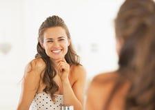 Donna sorridente che guarda in specchio in bagno immagini stock