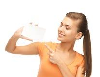 Donna sorridente che indica alla carta in bianco bianca Fotografie Stock Libere da Diritti